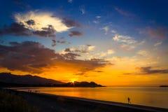 Заход солнца и тренировка на пляже Raglan Оно известный за свой серфинг, и вулканический пляж отработанной формовочной смеси стоковые фото