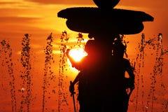 Заход солнца и фонтан, падения воды Стоковые Фото
