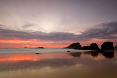 заход солнца красного цвета пляжа adraga стоковые фото