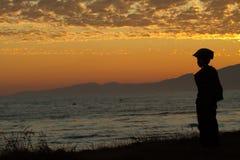 заход солнца моря мальчика Стоковые Фото