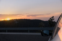 Заход солнца над горой увиденной от внешней стороны автомобиля Стоковые Фотографии RF