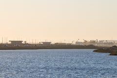 Заход солнца над заболоченными местами Bolsa Chica с шоссе Тихоокеанского побережья на заднем плане Стоковое Изображение RF