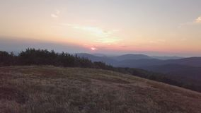 Заход солнца над лугом в виде с воздуха ландшафта гор акции видеоматериалы