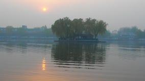 Заход солнца над озером в Пекин, Китаем Houhai Солнечный свет отражая со струясь воды сток-видео