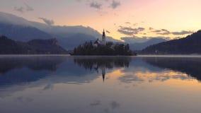 Заход солнца над озером кровоточенным с церковью St Marys предположения на небольшом острове; Словения, Европа сток-видео