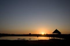 Заход солнца над озером & хатой на ходулочниках, Кенией Стоковые Фотографии RF