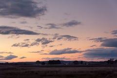 Заход солнца над полем страны с светлыми облаками в небе Стоковые Изображения RF