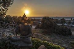 Заход солнца над представлением сидя защиты Будды стоковые изображения rf