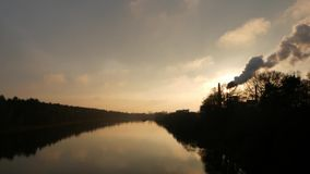 Заход солнца над рекой Дым от каминов фабрики Загрязнение окружающей среды видеоматериал