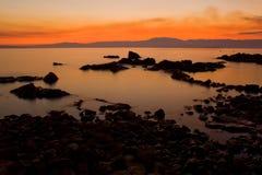 Заход солнца над утесистой береговой линией Стоковое фото RF
