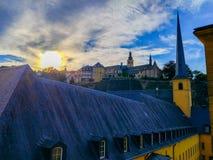 Заход солнца над церковью церков St. John St. John или St Джин du Grund в районе Grund, в старом городке Люксембурга, Европа стоковое изображение