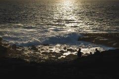 Заход солнца на Атлантическом океане при 3 люд наслаждаясь им сидя на утесах Стоковые Фотографии RF