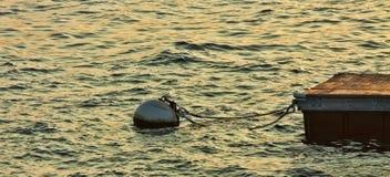 Заход солнца на воде при томбуй прикрепленный к доку Стоковые Фотографии RF