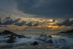 Заход солнца на море и волнах на камнях Стоковые Изображения RF