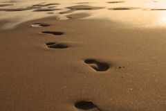 Заход солнца на море Следы ноги в песке Море, выравниваясь Утихомирите вниз лето моря остальных путешествием безшовное стоковое фото rf