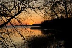 Заход солнца на озере - оранжевое небо было создано стоковое изображение