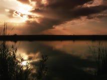 Заход солнца на озере, thunderclouds и траве на береге Стоковое фото RF