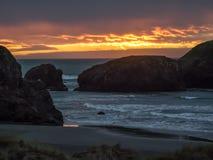 Заход солнца на песчаном пляже с стогами моря стоковые изображения rf