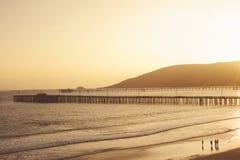 Заход солнца на пляже Авила с пристанью стоковые изображения