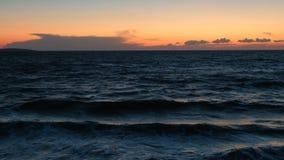 Заход солнца на пляже Спокойная идилличная сцена золотого захода солнца над морем, волны медленно брызгая акции видеоматериалы