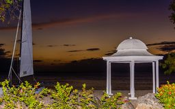 Заход солнца на пляже с катамараном и газебо Стоковое фото RF