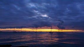 Заход солнца на пляже с целью шлюпок стоковое фото