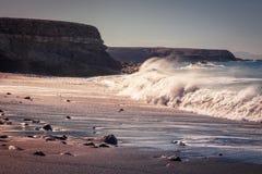 Заход солнца на пляже умерших в Ajuy, куда волны сломали сильно, Фуэртевентура, Канарские островы, Испания стоковое изображение rf