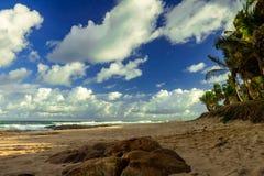 Заход солнца на сиротливом пляже Небо заселенное белыми облаками сравнивает с синью моря стоковые фотографии rf
