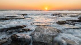 Заход солнца на скалистом пляже, Кипре стоковая фотография rf