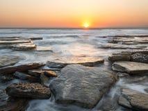 Заход солнца на скалистом пляже, Кипре стоковое изображение