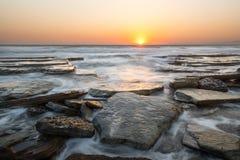 Заход солнца на скалистом пляже, Кипре стоковое изображение rf