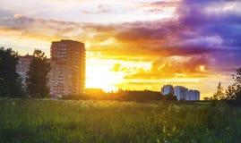 Заход солнца на фоне блока квартир, жилых домов, в Европе в поле, новые дома Стоковая Фотография