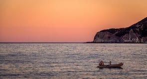 Заход солнца на horizont с маленькой лодкой Стоковое Фото