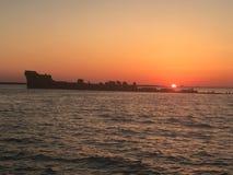 Заход солнца на sunken корабле стоковое изображение