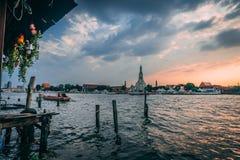 Заход солнца на Wat Arun Chao Phraya с Longboat на заходе солнца Взгляд от ресторана с некоторыми туристами внутрь стоковые фотографии rf