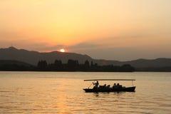 заход солнца озера шлюпки западный стоковые фото