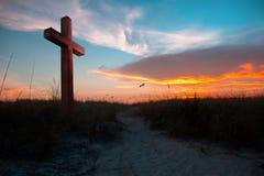 Заход солнца освещая крест стоковые изображения