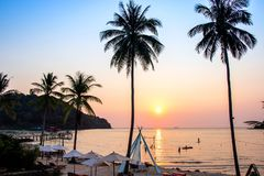 Заход солнца отражая на переднем плане поверхности воды с bao челки ao зоны кокосовых пальм на острове kood Koh район Trat стоковые изображения rf