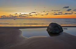 Заход солнца пляжа золотое небо с завальцовкой волны Стоковая Фотография