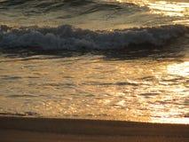Заход солнца пляжа небо захода солнца с завальцовкой волны Стоковое Фото