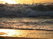 Заход солнца пляжа небо захода солнца с завальцовкой волны Стоковое Изображение