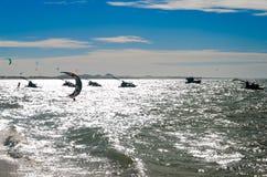 Заход солнца при серферы змея наслаждаясь морем Стоковое Изображение