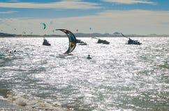 Заход солнца при серферы змея наслаждаясь морем Стоковые Фото
