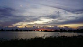 Заход солнца промежутка времени за двигая облаком Дает красивый золотой свет над болотами видеоматериал