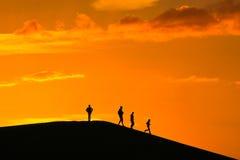 заход солнца семьи совместно гуляя Стоковое фото RF