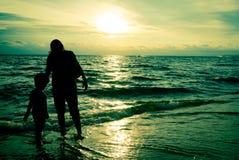 Заход солнца силуэта матери и сына на пляже Стоковые Фотографии RF