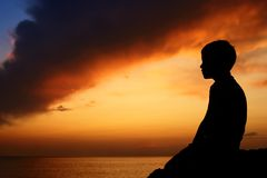 заход солнца силуэта моря мальчика Стоковое Изображение RF