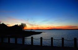 заход солнца силуэта lakehouse Стоковые Фото