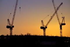 заход солнца силуэтов кранов конструкции промышленный Стоковые Изображения