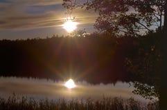Заход солнца, солнце отраженное в воде, солнце выходить деревья Стоковое Изображение RF